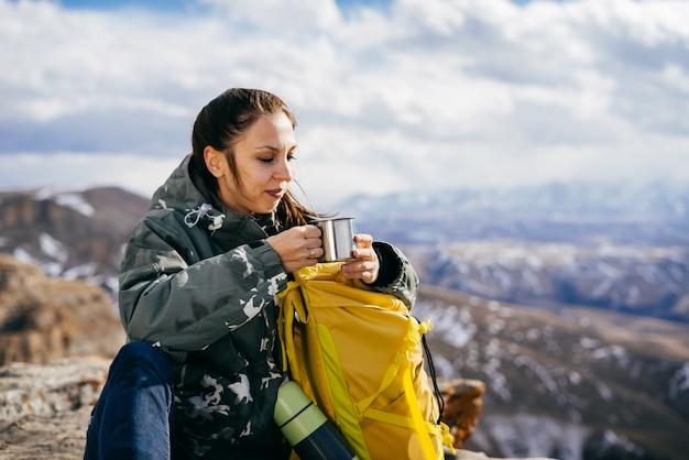 Aktywna młoda dziewczyna w ciepłej kurtce podróżuje po górach, cieszy się przyrodą, pije gorącą herbatę z termosu