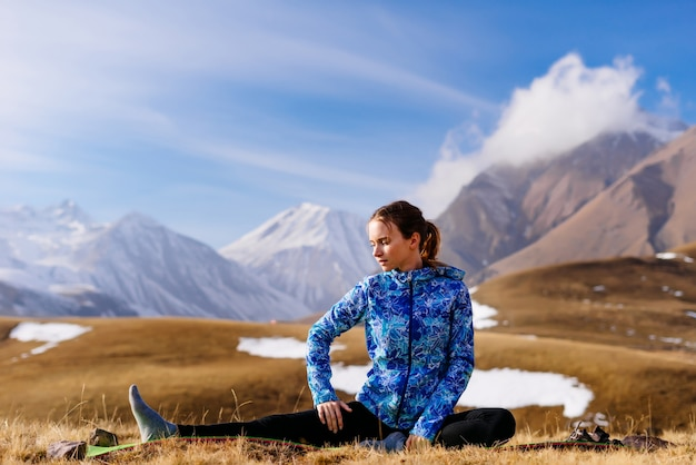 Aktywna młoda dziewczyna w niebieskiej kurtce uprawiająca jogę na tle kaukaskich gór