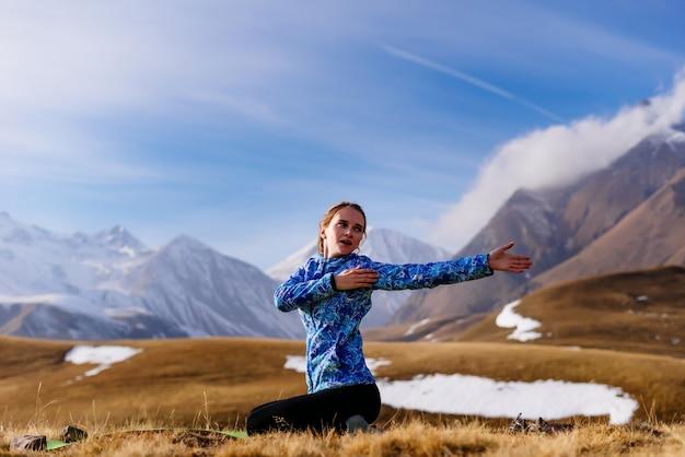 Aktywna młoda dziewczyna w niebieskiej kurtce zajmuje się jogą na tle gór kaukazu, podróżuje