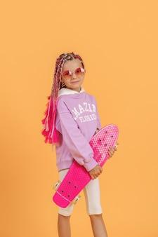 Aktywna młoda dziewczyna w różowej koszuli i białych spodenkach, trzymając deskorolkę na żółtym tle