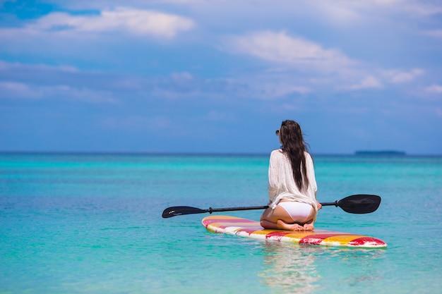 Aktywna młoda kobieta na wstań wiosła pokładzie