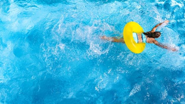 Aktywna młoda kobieta pływa w basenie z nadmuchiwanym pierścieniem