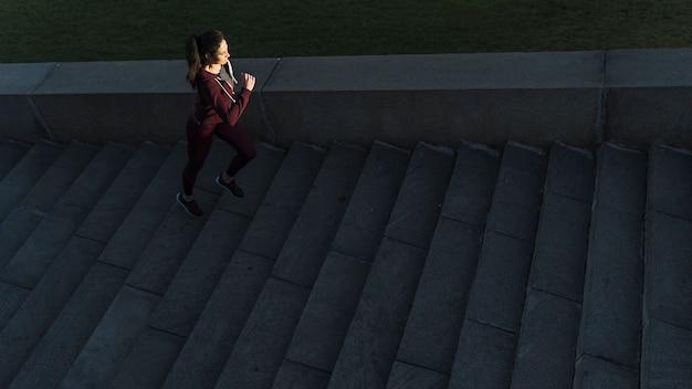 Aktywna młoda kobieta wspinaczka po schodach