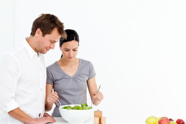 Aktywna para przygotowuje sałatkę na obiad