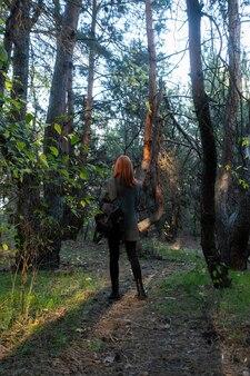Aktywna piękna rudowłosa dziewczyna spaceru w lesie. podróżnik kobieta z plecakiem spacery po niesamowitym lesie, koncepcja podróży, miejsce na tekst, chwila atmosfery. dzień ziemi