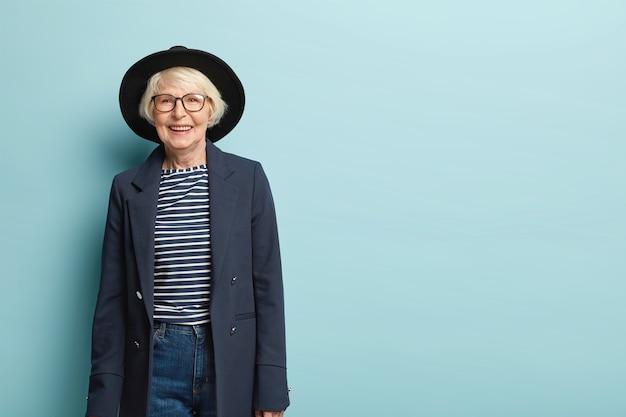 Aktywna, radosna stylowa nauczycielka przechodzi na emeryturę, nosi kapelusz i formalną marynarkę, ciesząc się z gratulacji od kolegów