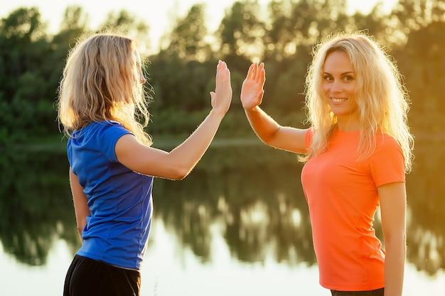 Aktywna rodzina na świeżym powietrzu. dwie elastyczne kręcone blondynki piękna kobieta bliźniaczki w stylowych strojach sportowych rozciąganie praca zespołowa i rozgrzewka piątka na stadionie jezioro ładny zachód słońca tło park