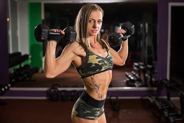 Aktywna sportowa kobieta lekkoatletycznego z hantlami pompowania mięśni biceps koncepcja styl życia treningu fitness sport