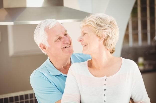 Aktywna starsza para obejmuje w kuchni