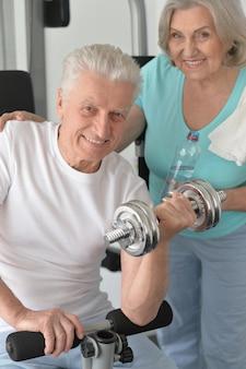 Aktywna uśmiechnięta para starszych ćwiczących w siłowni