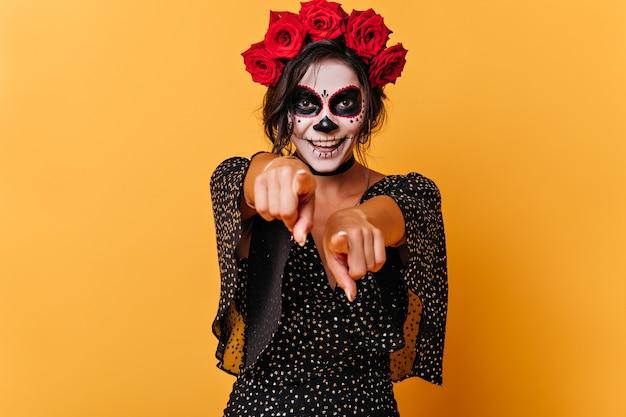 Aktywna wesoła brunetka wskazuje palcami na aparat. portret uśmiechniętego europejskiego modela ze sztuką twarzy na halloween.