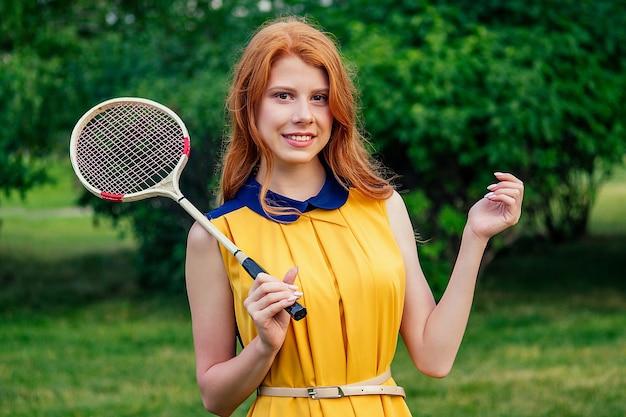 Aktywna wesoła piękna młoda ruda irlandzka norweska osoba płci żeńskiej w żółtej sukience i różowej tenisowej rakietce do badmintona w letnim parku