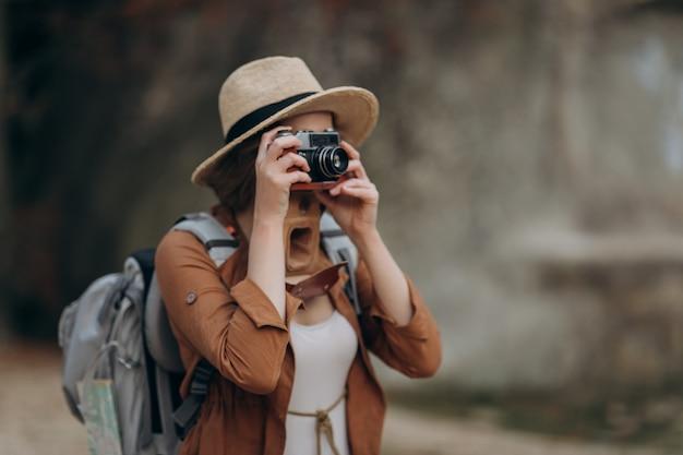 Aktywna zdrowa kaukaska kobieta robi zdjęcia kamerą filmową na skałach leśnych