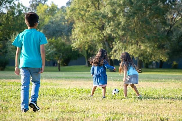 Aktywne dzieci grające w piłkę nożną na trawie w parku miejskim. pełna długość, widok z tyłu. koncepcja dzieciństwa i aktywności na świeżym powietrzu