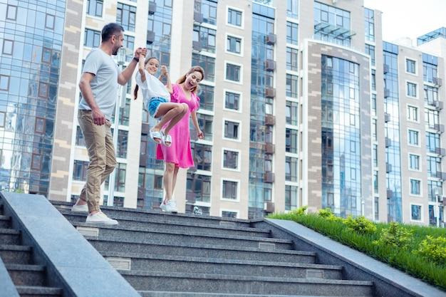Aktywne dziecko. zachwycona miła dziewczyna bawiąca się podczas skakania po schodach