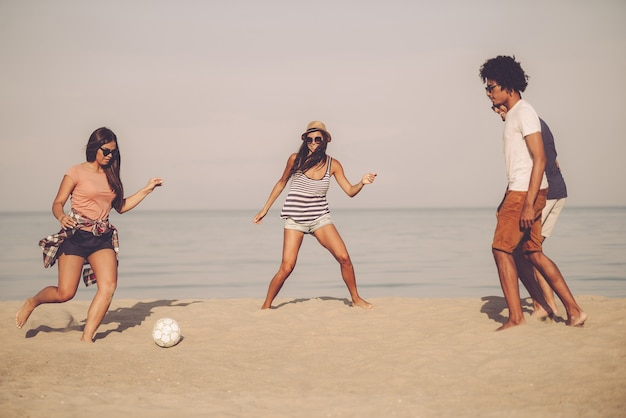 Aktywne gry z przyjaciółmi. grupa wesołych młodych ludzi bawiących się piłką nożną na plaży z morzem w tle