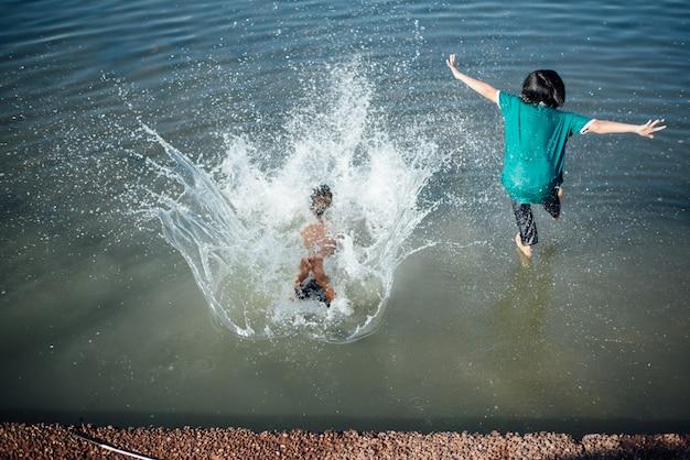 Aktywni chłopcy skaczą z kłód w wodę.