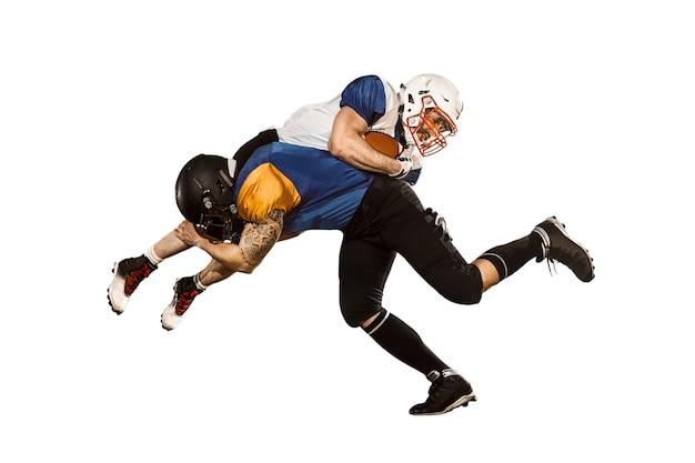 Aktywni dwaj gracze futbolu amerykańskiego na białym tle dopasuj kaukaskich mężczyzn w mundurach