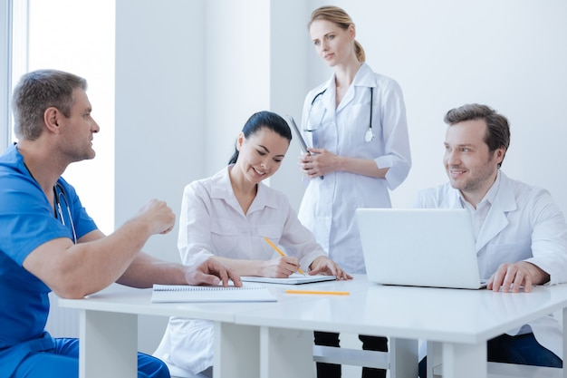 Aktywni lekarze z inicjatywą energetyczną pracujący w szpitalu i cieszący się rozmową, dzieląc się doświadczeniami medycznymi i robiąc notatki