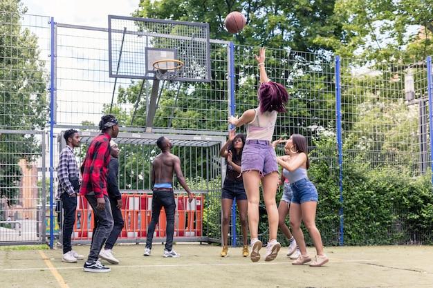 Aktywni młodzi ludzie różnych narodowości grający w koszykówkę razem na świeżym powietrzu