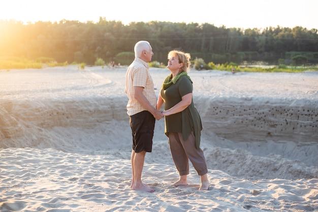 Aktywni seniorzy całują się w letniej naturze, para seniorów odpoczywa w okresie letnim. opieka zdrowotna na emeryturze stylu życia para miłość razem