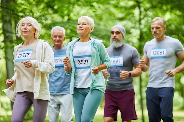 Aktywni starsi mężczyźni i kobiety spędzają razem letni dzień w parku, biegnąc w maratonie, średni strzał
