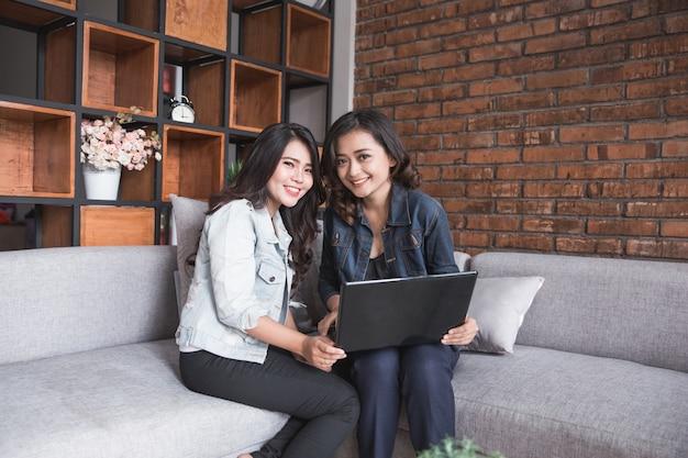 Aktywność dwa żeńskiego przyjaciela używa laptop
