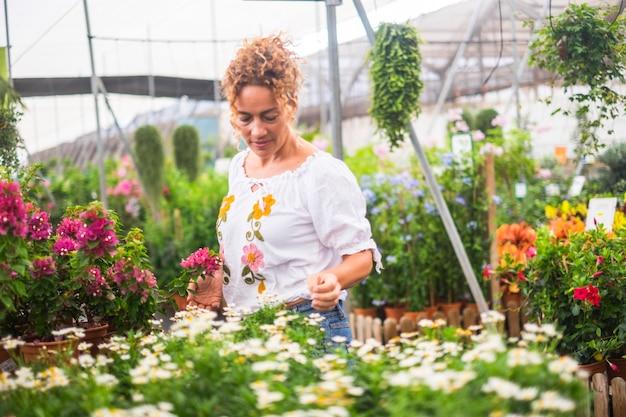 Aktywność ogrodnicza z piękną dorosłą kobietą w środku sklepu z kwiatami i roślinami sklep biznes miejsce
