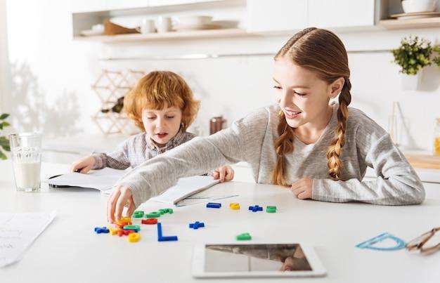 Aktywność twórcza. jasna, pełna entuzjazmu, ładna dziewczyna, która podczas wspólnego poranka w domu uczy swojego brata obliczeń za pomocą specjalnego formularza gry