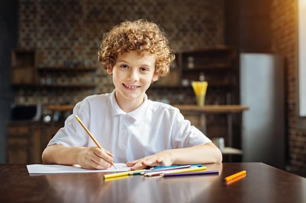 Aktywność twórcza. portret pracowitego młodzieńca siedzącego przy drewnianym stole i patrząc w kamerę z radosnym uśmiechem na twarzy podczas pracy nad nowym arcydziełem kolorowymi ołówkami.