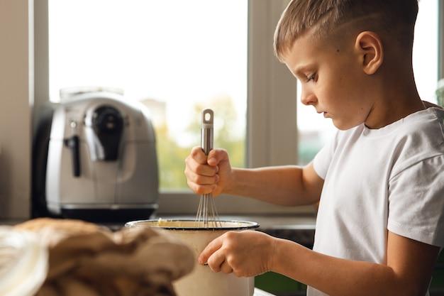 Aktywność wewnętrzna. młody chłopiec dziecko gotowanie w kuchni. robić ciastka lub herbatniki