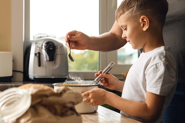 Aktywność wewnętrzna. młody chłopiec dziecko gotowanie w kuchni z matką. robić ciastka lub herbatniki