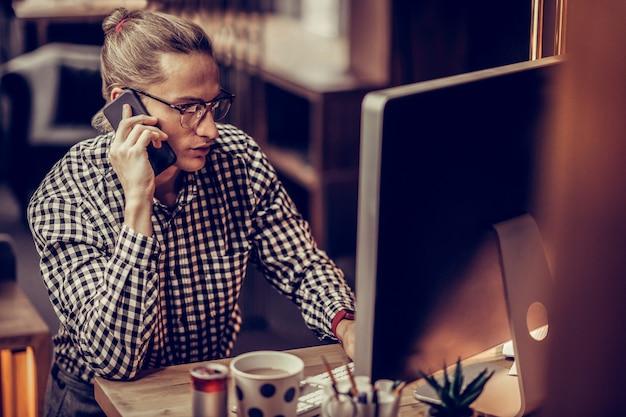 Aktywność zawodowa. skoncentrowany młody mężczyzna siedzi w miejscu pracy, patrząc na komputer