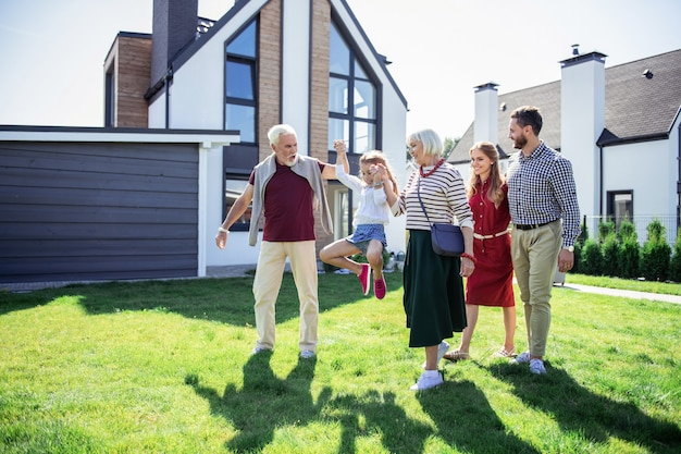 Aktywności rodzinne. aktywny dziadek patrząc na swoją wnuczkę podczas wspólnego spaceru