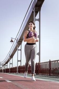 Aktywności sportowe. radosna pozytywna kobieta uśmiechnięta podczas biegu na moście