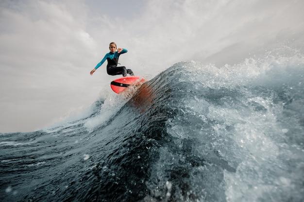 Aktywny chłopak ubrany w strój kąpielowy surfing skoki w górę na tablicy pomarańczowy