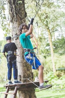 Aktywny dzielny chłopiec, cieszący się wychodzącą wspinaczką w parku rozrywki na szczycie drzewa