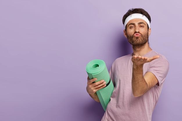 Aktywny facet przesyła buziaka, utrzymuje zaokrąglone usta, wyciąga dłoń, trzyma matę, lubi trening fitness lub zajęcia jogi