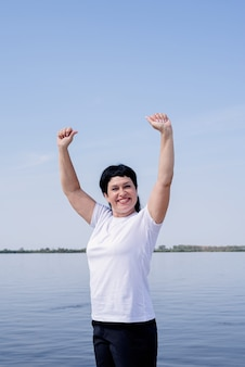 Aktywny i szczęśliwy starszy kobieta ćwicząc w pobliżu rzeki stojąc z rękami do góry
