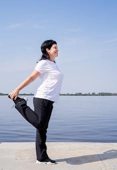 Aktywny i szczęśliwy starszy kobieta robi rozciąganie w pobliżu brzegu rzeki
