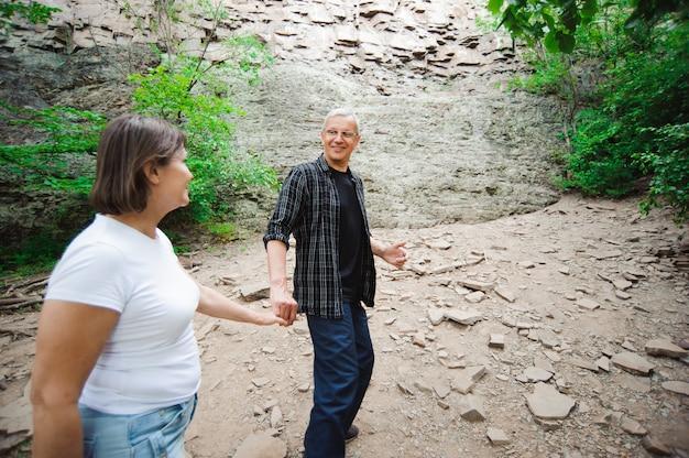 Aktywny kochający starszy pary odprowadzenie w pięknym lato lesie - aktywny emerytura pojęcie