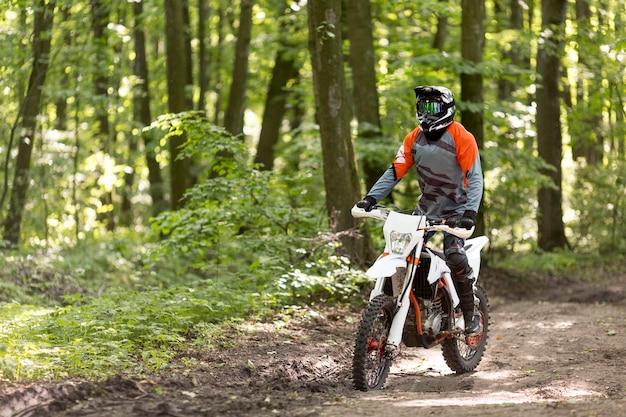 Aktywny mężczyzna jedzie motocykl w lesie