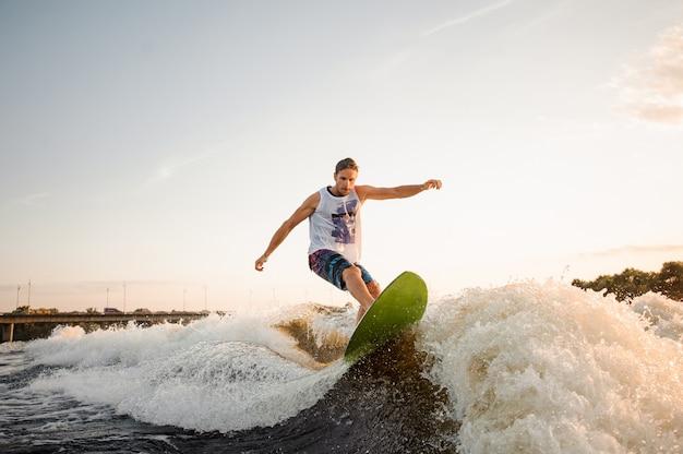 Aktywny mężczyzna jedzie na zielonym wakesurfingu po falach rzeki