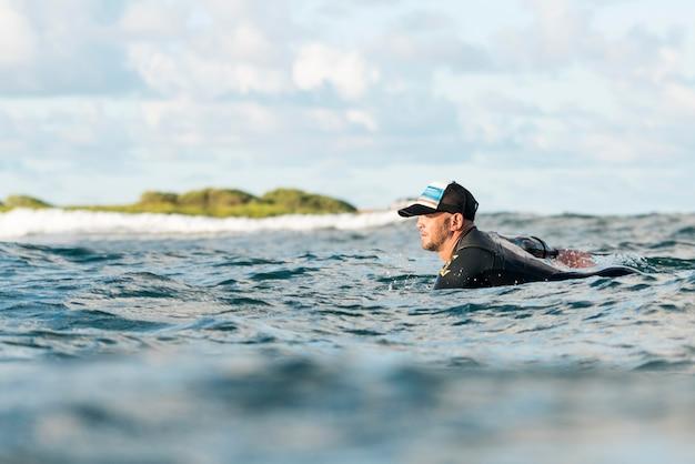 Aktywny mężczyzna w specjalnym sprzęcie przebywający na desce surfingowej