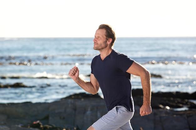 Aktywny mężczyzna w średnim wieku działa przez morze
