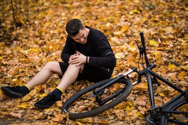 Aktywny młody człowiek trzymając się za ranę lub złamaną nogę leżąc na leśnej ścieżce jesienią na rowerze