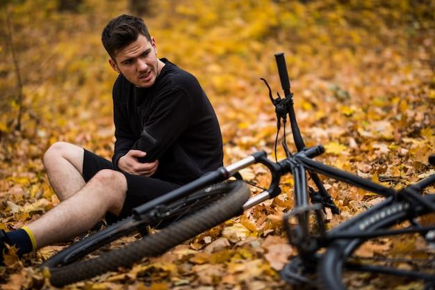 Aktywny młody człowiek trzymając się za zranione lub złamane ręce, leżąc na leśnej ścieżce jesienią na rowerze