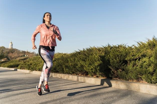 Aktywny młody żeński biegać plenerowy