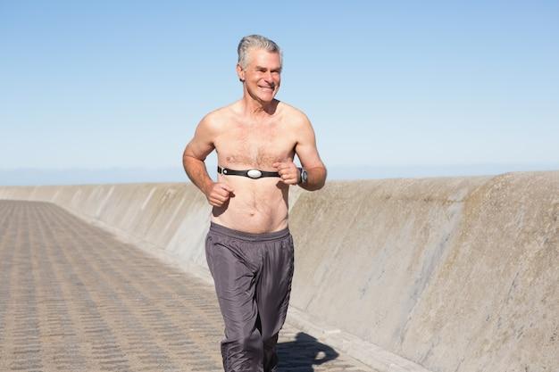 Aktywny półnagi starszy człowiek jogging na molo