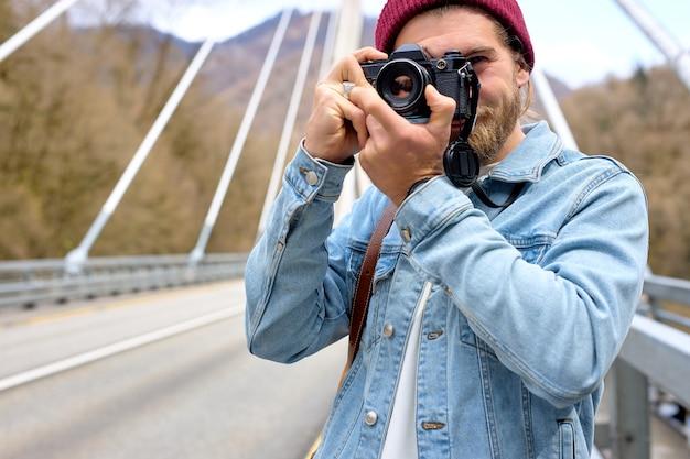 Aktywny przystojny fotograf mężczyzna robienia zdjęć na aparacie podczas chodzenia, podróży. caucasian podróżnik podróżuje samotnie, używając filmowej kamery retro. ekoturystyka, turystyka. kopia przestrzeń, portret